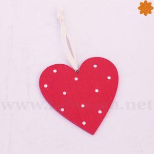 Colgante de madera que es un corazón rojo con topos blancos