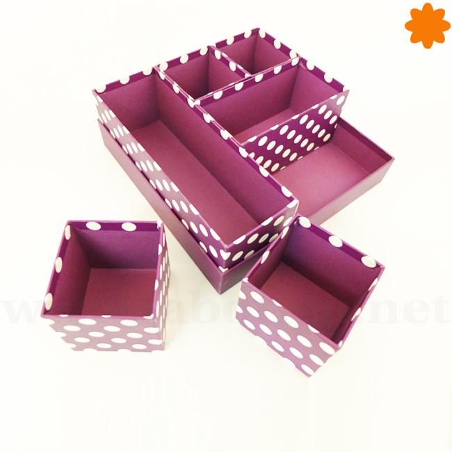Caja de cartón de color morado con topos blancos