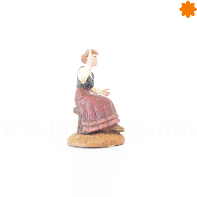 Figurita de una campesina sentada con un vestido rojo