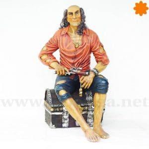 Figura de un pirara armado sentado en un cofre
